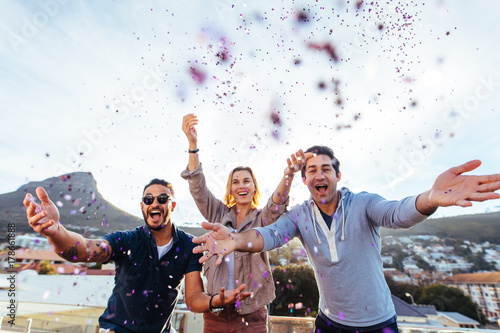 Group of friends enjoying party with confetti Poster