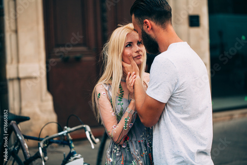 Plakat londe girl and Hipster handsome man with beard hugging and kissing on the city s