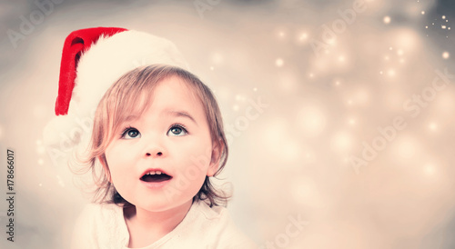 Happy toddler girl with Santa hat in snowy night
