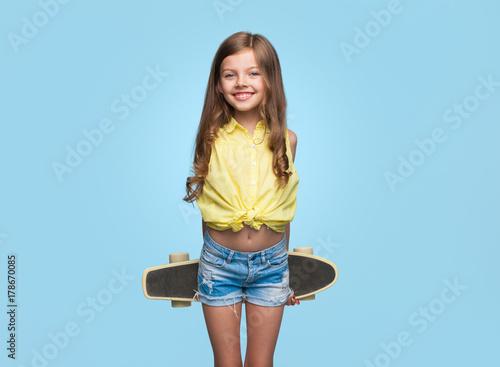 Cheerful girl with longboard on blue