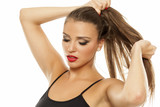 young beautiful woman tightens hair in ponytail - 178671060