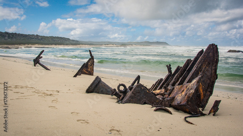 Fotobehang Beige The rusty remains of a wreck of an old trawler on the beach at Cape Point, South Africa