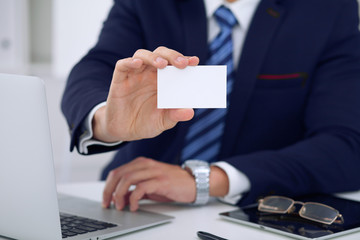 Unknown businessman or lawyer  giving a business card while sitting at the table, close-up. He offering partnership and success deal