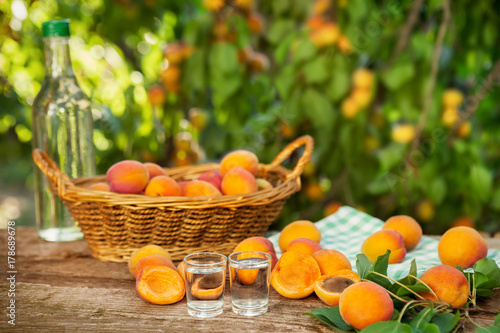 Fruit brandy and raw apricots on table