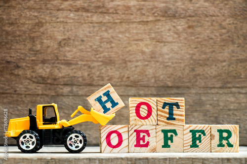 Keuken foto achterwand Boodschappen Toy plastic bulldozer hold letter block H to complete wording hot offer on wood background