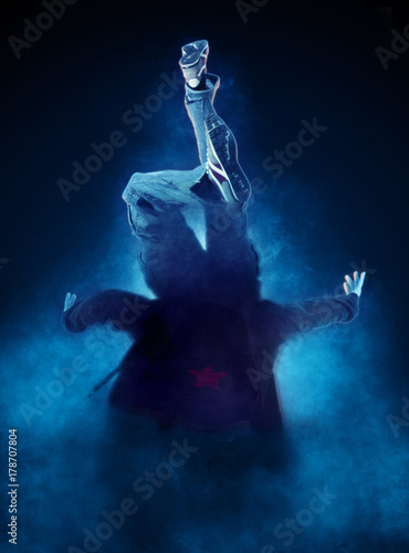 Young man break dancing on dark smoke background Poster