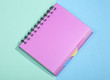 Notepad with pink cover on a colored background