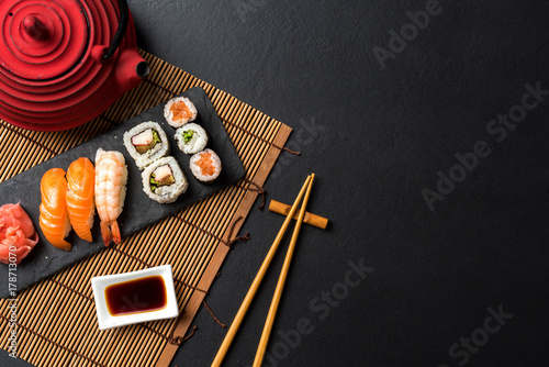 Fotobehang Sushi bar Set of sushi with wasabi, soy sauce and teapot on black stone background. Top view
