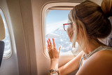 Young woman enjoying the view through the aircraft window sitting during the flight in the airplane - 178713815