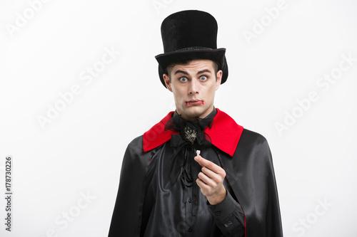 Vampire Halloween Concept - Portrait of handsome caucasian Vampire hurting lose his vampire tooth Poster