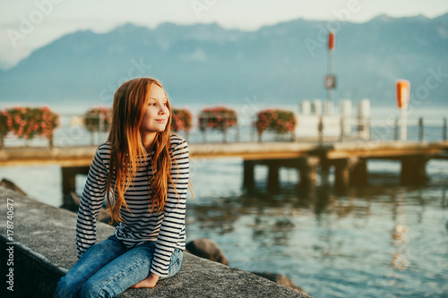 Cute little redheaded girl resting by lake Geneva at sunset, image taken in Laus Poster