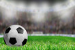 Soccer Ball on Field With Brightly Lit Stadium Background and Copy Space