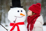Adorable little girl building a snowman in beautiful winter park. Cute child playing in a snow. - 178748010