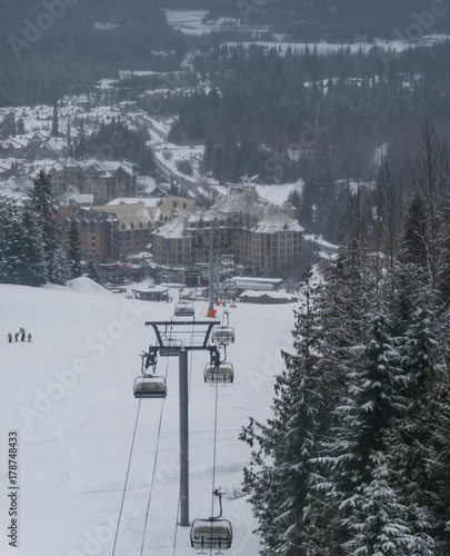 Keuken foto achterwand Canada Ski chairlift and going up snow covered mountain between trees from village below