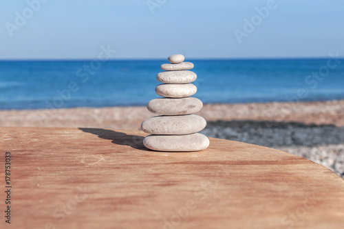 Foto op Canvas Zen Beach round pebble stone set balance arrangement like zen symbol on wooden table
