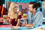 attractive romantic couple holding beers at mexican restaurant about to eat tacos - 178759266