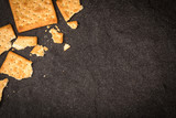 Top view of the whole wheat crackers flat lay as border on black stone of frame for baked food background - 178761248