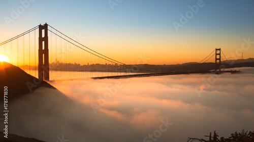 Spektakularny wschód słońca przy Golden Gate Bridge z niską mgłą.