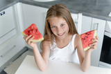 cute little girl eats a watermelon in the kitchen