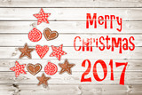Christmas greeting card 2017, rustic ornaments on wood planks background creating the shape of a Christmas tree - 178785061