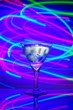 Leinwanddruck Bild - Glass with a cocktail with ice against a background of abstract illumination of colored neon