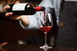 Waiter pouring red wine into wineglass. Sommelier pours alcoholic drink