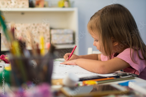 little girl draws pencils at home