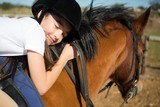 Cute girl embracing horse in the ranch