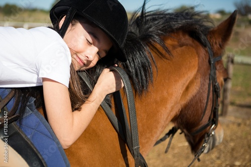 Cute girl embracing horse in the ranch Poster