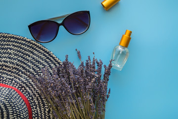 A bouquet of dry lavender in kraft paper on a blue background with a bottle of perfume, sunglasses and a hat, symbolizing summer and France. Flat lay, top view.