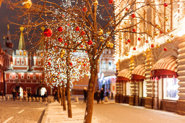 Streets of Moscow decorated for New Year and Christmas celebration. Tree with bright red and yellow balls. Buildings with light bulbs.