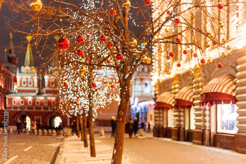 Tuinposter Moskou Streets of Moscow decorated for New Year and Christmas celebration. Tree with bright red and yellow balls. Buildings with light bulbs.