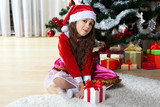 Celebration of Christmas, winter holidays and people concept. Happy young girl with gifts in boxes sitting near a decorated Christmas tree at home - 178833035
