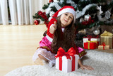 Celebration of Christmas, winter holidays and people concept. Happy young girl with gifts in boxes sitting near a decorated Christmas tree at home - 178833054