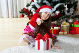 Celebration of Christmas, winter holidays and people concept. Happy young girl with gifts in boxes sitting near a decorated Christmas tree at home - 178833087