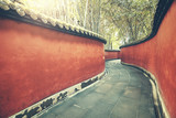 Curvy red wall passage surrounded by bamboo forest, color toning applied, Wuhou Temple, Chengdu, China.