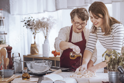 Grandmother adding oil to dough - 178837210