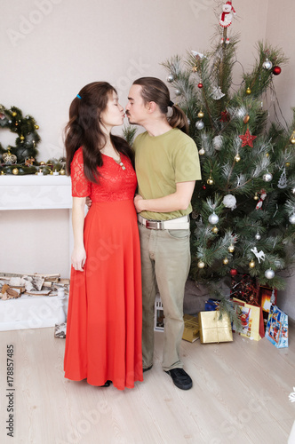 Plakat pregnant wife and husband kissing each other, happy young family portrait in Chr