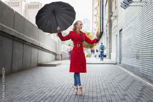 Ballerina with umbrella on city street Poster