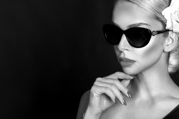 Portrait of beautiful woman with stunning face with flower in hair and in elegant sunglasses, on black background