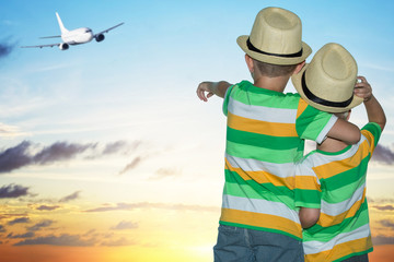 Two brothers at the airport watching the plane taking off.