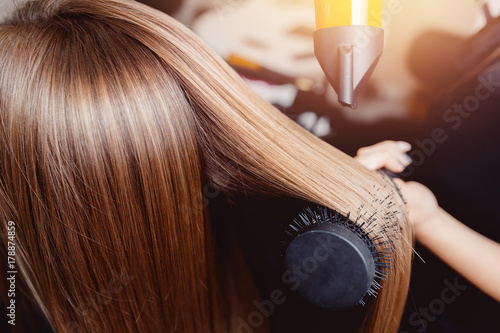 Close-up of hair dryer for hair drying, concept hair salon, female stylist. © Parilov