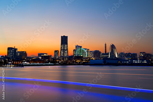 The city skyline at sunset of Yokohama, Japan with all the buildings illuminated and streaks from boat traffic on the water
