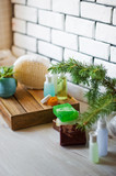 Spa accessories. Sprigs of a Christmas tree, many multi-colored pieces of soap, many different shapes of bottles for a bathroom. Body scrub. Light brick and white wooden as a background - 178918089