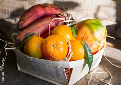 Exotic fruits with red banana on old retro wooden boards still life