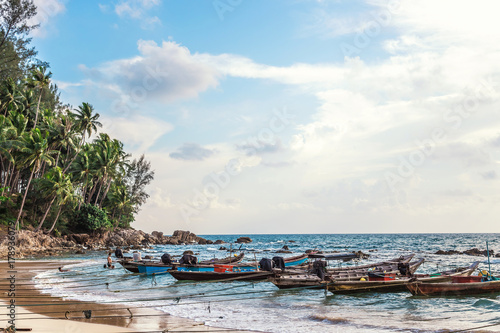 Sandy beach with colorful fishing boats at sunset. Phuket Thailand © PRASERT