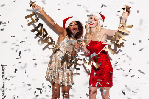 Screaming happy young women friends holding happy new year garland.