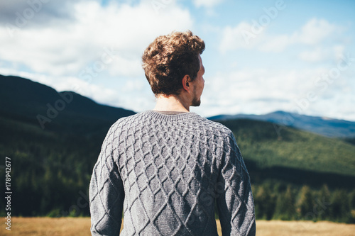 Foto op Canvas Grijze traf. young man in grey knitted sweater stands back to the camera looking on the mountains