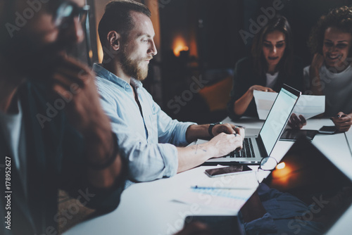 Businessman working together with project team at meeting room at night office.Horizontal.Blurred background.