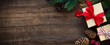 Christmas banner with gifts, fir branches pine cones and seasonal ornaments against gark rustic wooden background. Overhead view with copy space for your text